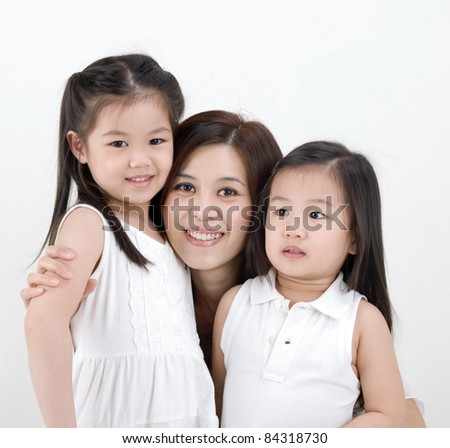 beautiful asian mother hugging her daughters