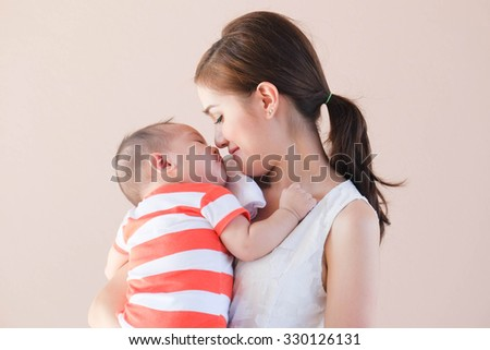 Beautiful Asian mother kiss her son on pastel isolate background. - stock photo