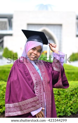 Beautiful asian muslim college graduate with degree after convocation ceremony - stock photo