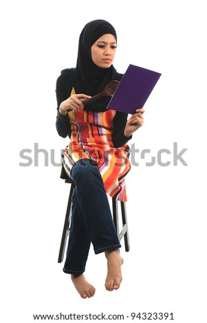 Beautiful asian muslim woman seat and read the cook book isolated white background