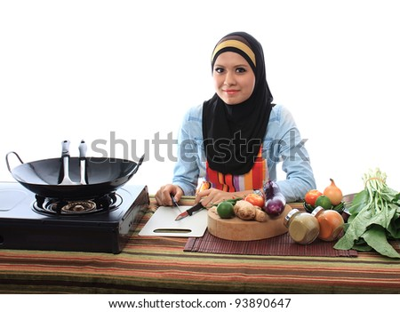 Beautiful asian muslim woman smile while looking to the camera in the kitchen isolated white background - stock photo