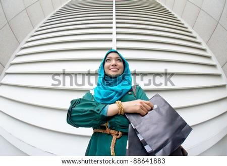 Beautiful Asian Muslim woman with shopping bag - stock photo