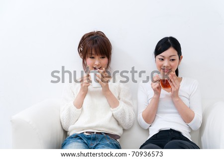 beautiful asian sisters relaxing on the sofa - stock photo