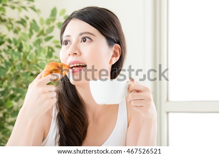 beautiful asian smile girl eating croissant and enjoy coffee, healthy food concept indoor background