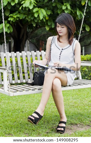 Beautiful Asian student woman on white wooden swing.
