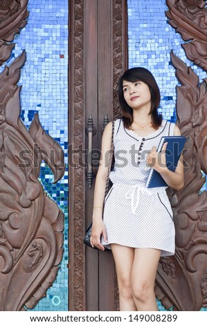 Beautiful Asian student woman with wooden door background.