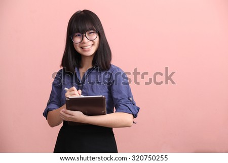 Beautiful Asian teen writing tablet smile