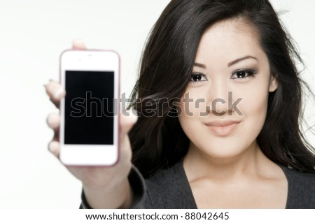 beautiful asian teenager holding her phone toward camera, white background, phone is soft focus - stock photo
