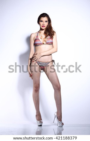 Beautiful Asian Thai Model Woman in Curly Brown Hair Bikini Sport Swim Suit Fashion Make Up with Accessory Shadow on White Background in Studio Lighting, Sexy Pose full body