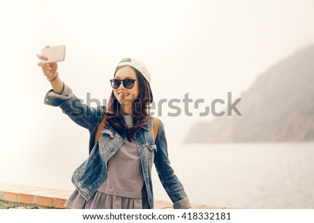 Beautiful Asian traveler taking selfie with ocean view background, soft warm light tone - stock photo