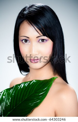 beautiful asian woman and leaves - stock photo