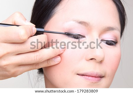 Beautiful  asian woman doing make-up on face with cosmetic brush.