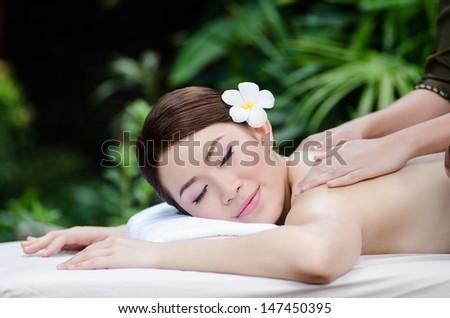 Beautiful Asian woman doing spa massage - stock photo