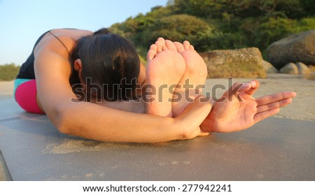 Beautiful asian woman doing yoga on the beach - stock photo