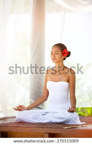 Beautiful  Asian woman doing yoga outside under baldachin - stock photo