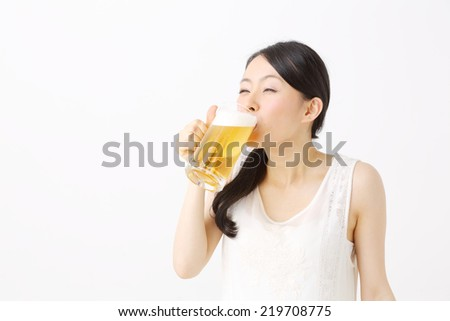 beautiful asian woman drinking a beer - stock photo