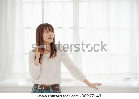 beautiful asian woman drinking a glass of tea