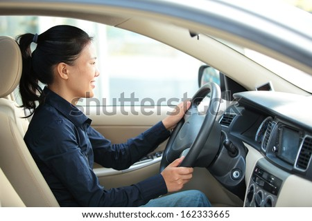 beautiful asian woman driving a car