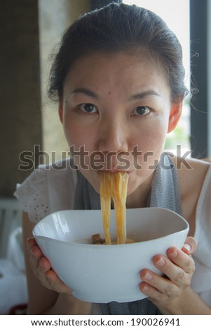 Beautiful Asian woman eating noodles with spicy. - stock photo