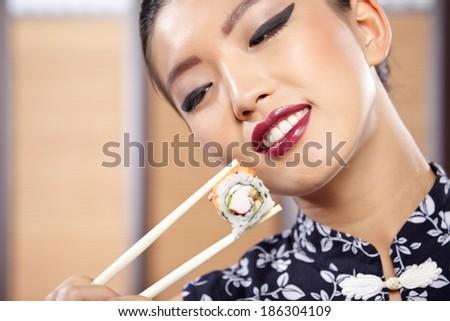 beautiful asian woman eating sushi with chopsticks - stock photo
