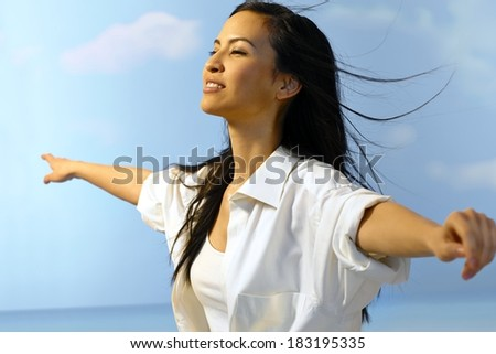 Beautiful Asian woman enjoying summertime outdoors, flying with arms wide open. - stock photo