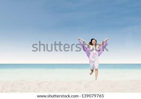 Beautiful asian woman enjoying the breeze by the sea in paradise - stock photo
