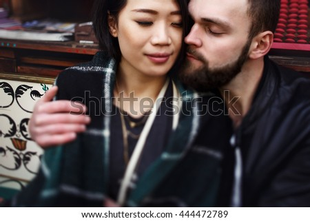 Beautiful asian woman & handsome man sitting in restaurant with a blanket