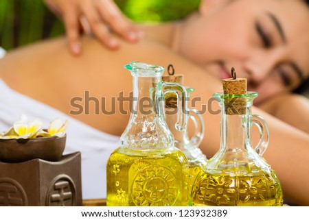 Beautiful Asian woman having a wellness back massage in a tropical setting and feeling visibly good about it - Essential oils are in the foreground - stock photo