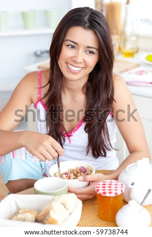 Beautiful asian woman having breakfast smiling at the camera sitting in the kitchen at home - stock photo