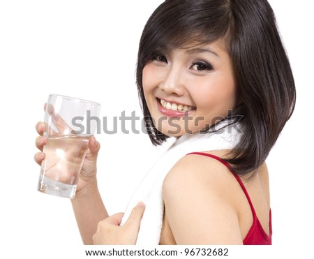 beautiful Asian woman holding a glass of water after exercise - stock photo