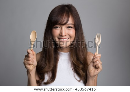 Beautiful asian woman holding spoon and fork, hungry woman,food and lifestyle concepts.