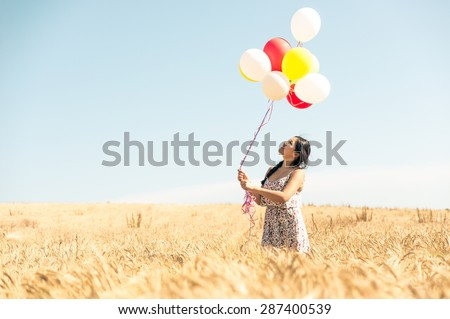 beautiful asian woman in a wheat field with air balloons. concept about airiness and carefree - stock photo
