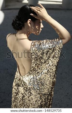 Beautiful asian woman in golden evening dress, Vietnam, wedding dress - stock photo