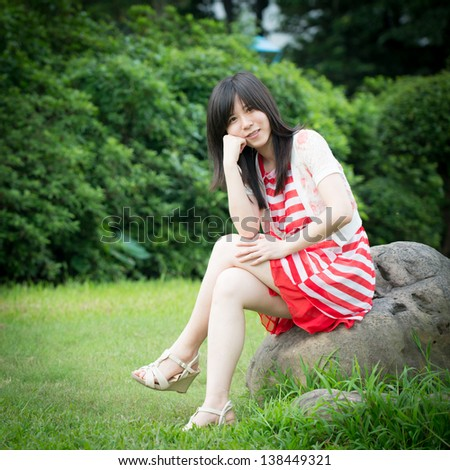 Beautiful Asian woman in red dress outdoor - stock photo