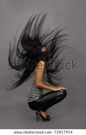 Beautiful asian woman in stripped vest on dark background - stock photo