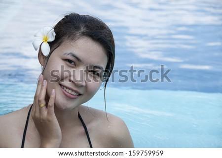 Beautiful Asian woman in swimming pool. - stock photo