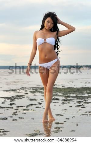 Beautiful asian woman in white bikini at sea - stock photo