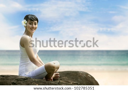 Beautiful Asian Woman in Yoga position smiling at beach
