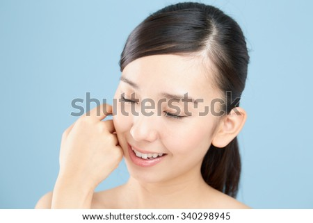 Beautiful asian woman isolated on blue background - stock photo