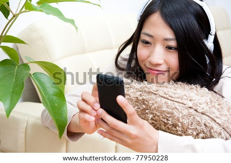 beautiful asian woman listening to music by smartphone - stock photo
