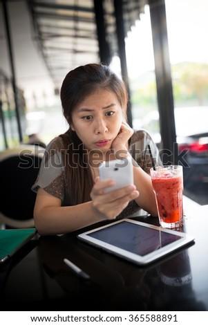 Beautiful Asian Woman Looking At Mobile Phone : Selective Focus - stock photo