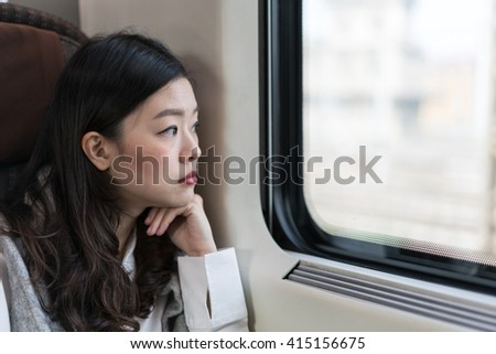 Beautiful asian woman looking out of train window, with copy space - stock photo