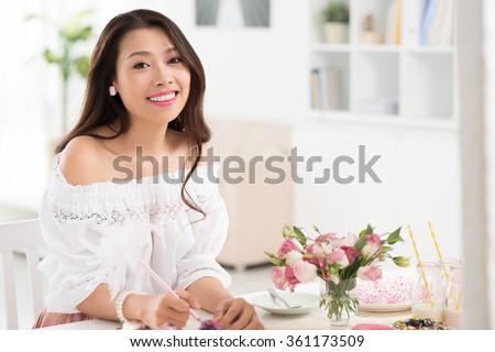 Beautiful Asian woman planning menu for buffet dinner - stock photo