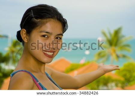 beautiful asian woman pointing to the sea - stock photo