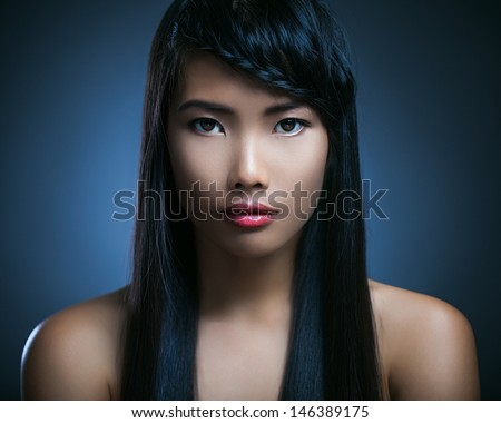 Beautiful Asian woman posing in front of a blue background. - stock photo