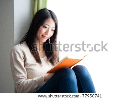 beautiful asian woman reading a book - stock photo