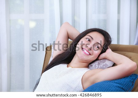 Beautiful Asian woman relaxing lying on a couch at home and smiling happy. Resting young female clasping her hands behind her head. - stock photo