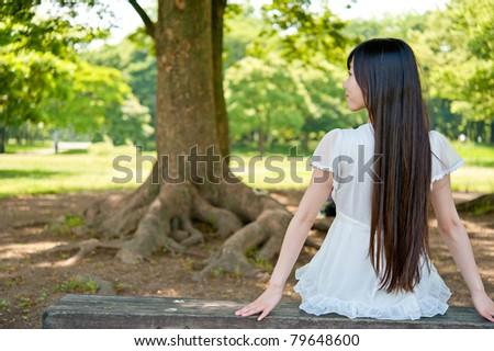 beautiful asian woman relaxing on the bench - stock photo