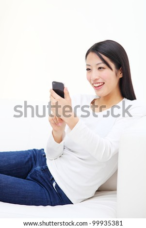 beautiful asian woman relaxing on the couch - stock photo