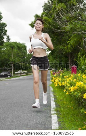 Beautiful Asian woman running on country road. - stock photo